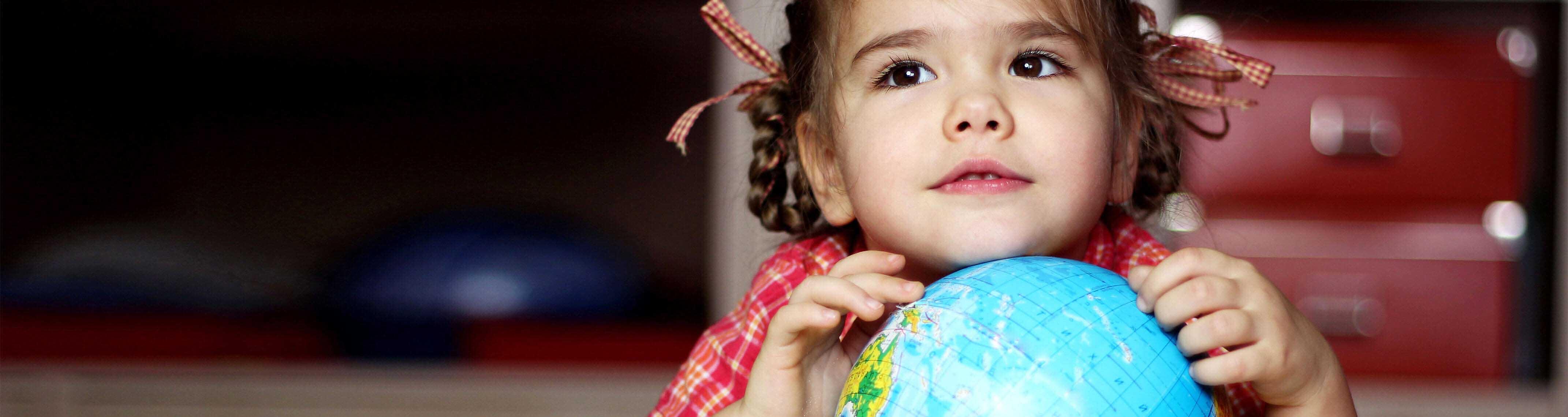 nina sosteniendo globo de la tierra